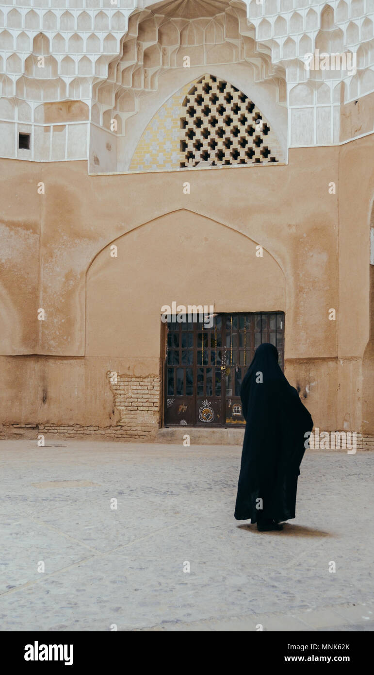 Woman in dark Muslim dress walking past a historical persian mosque with courtyard in Isfahan, Iran - Stock Image