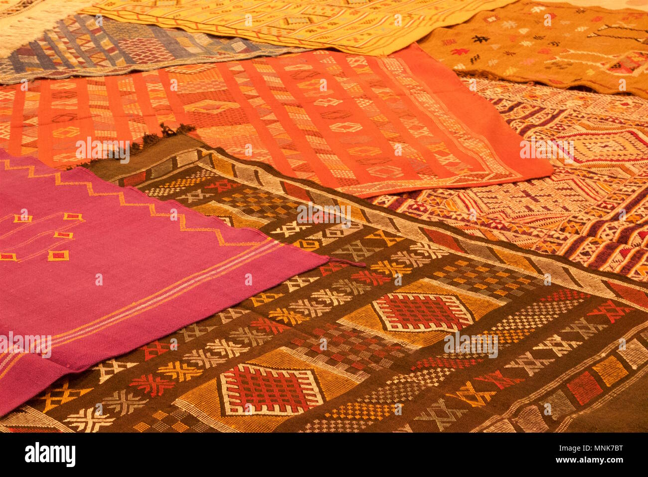 A collection of overlapping, patterned Moroccan rugs - Stock Image