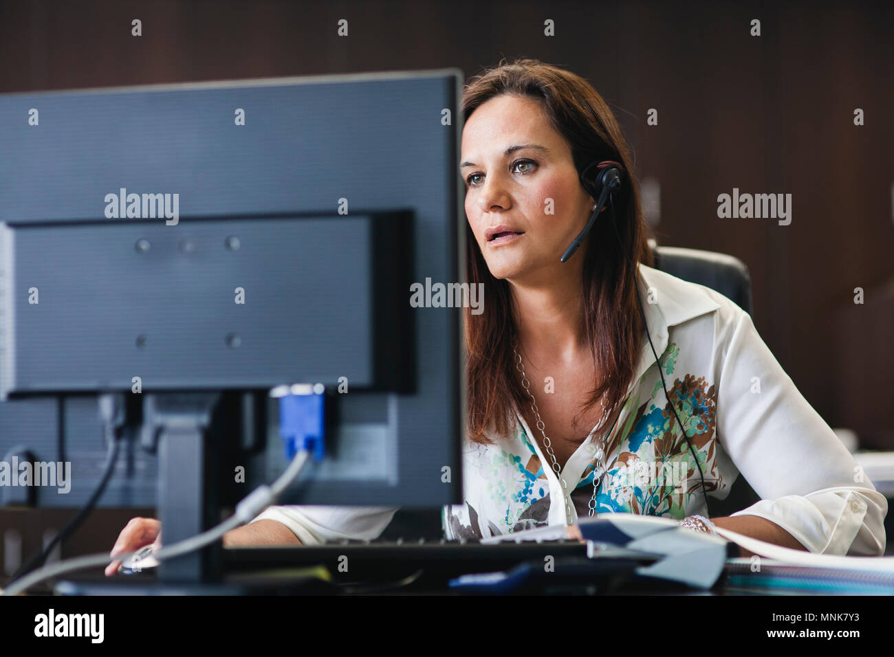 call center operator woman working in office with headphones and computer Stock Photo