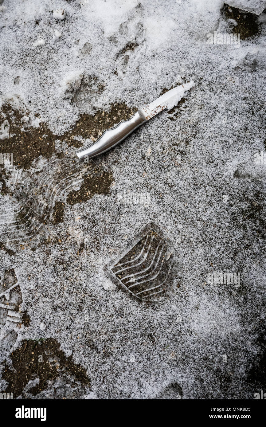Small kitchen knife and footprint in snow, conceptual knife crime image. - Stock Image