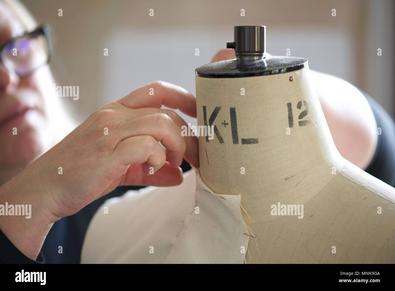 Pattern Maker (Fashion): a real Pattern Maker/Pattern Cutter at work on a calico toile on a model stand, or mannequin - Stock Image
