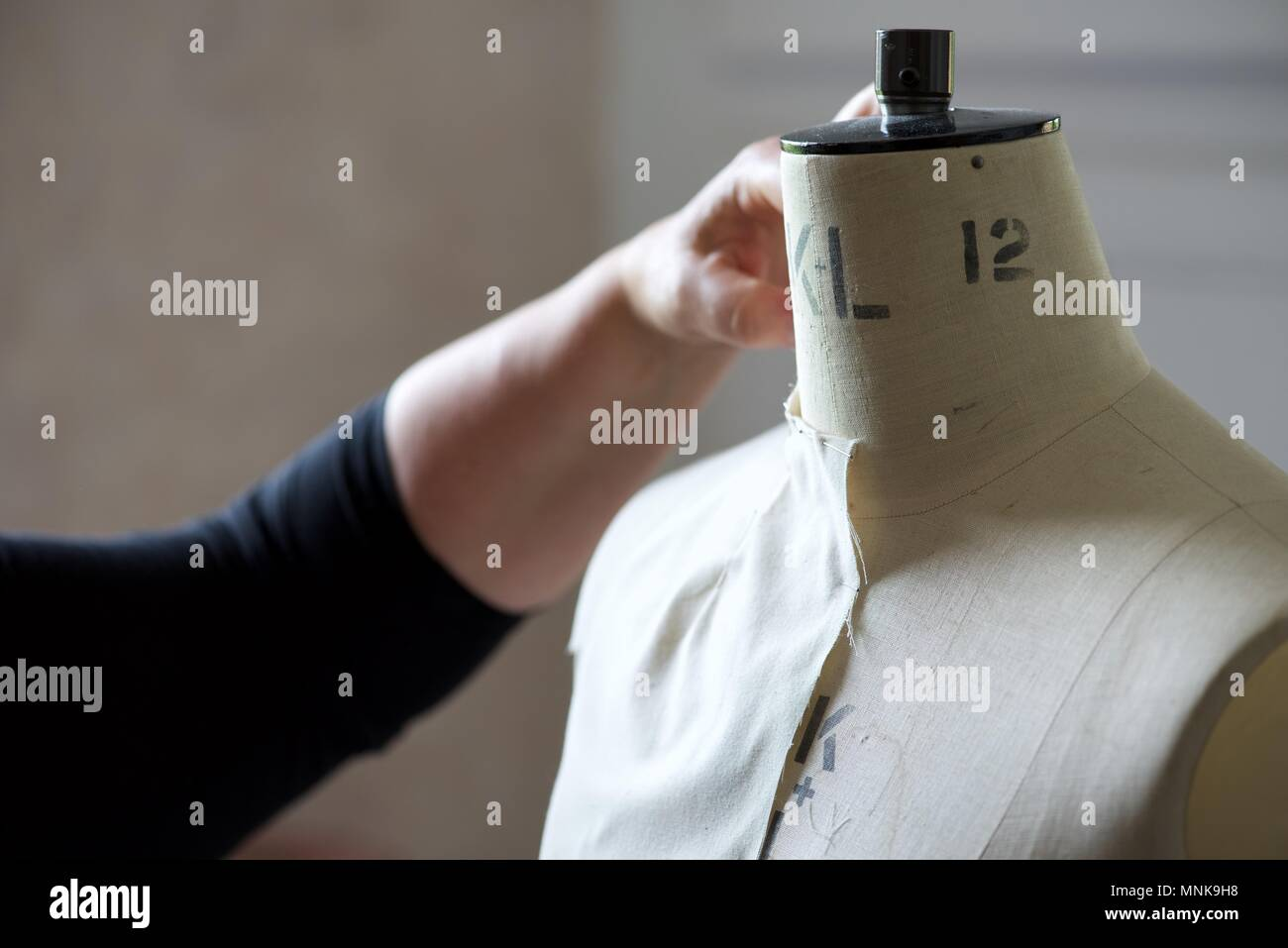 Pattern Maker (Fashion): a real Pattern Maker/Pattern Cutter at work on a calico toile on a model stand, or mannequin Stock Photo