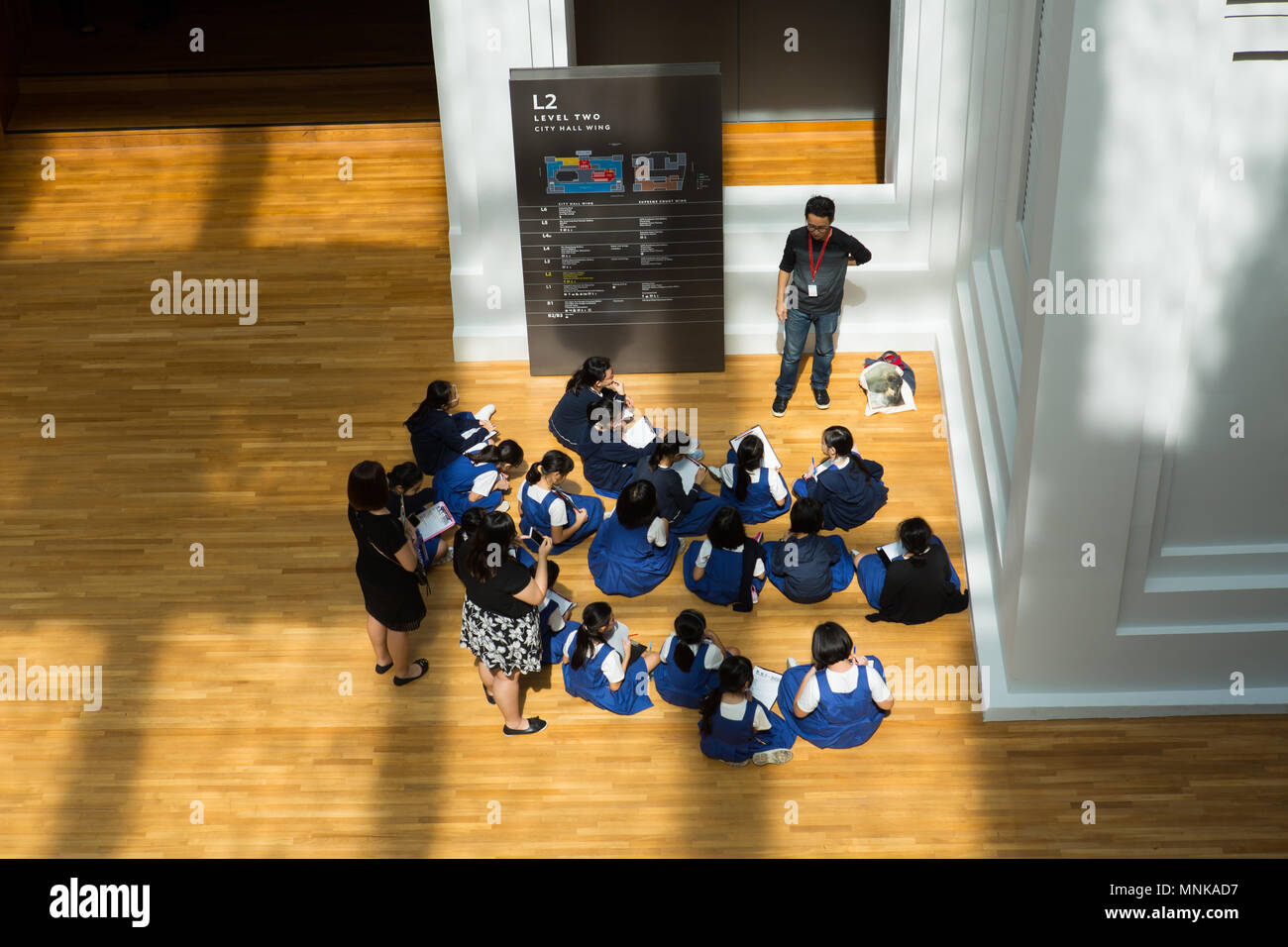 School students attending an indoor lecture in National Gallery Singapore - Stock Image