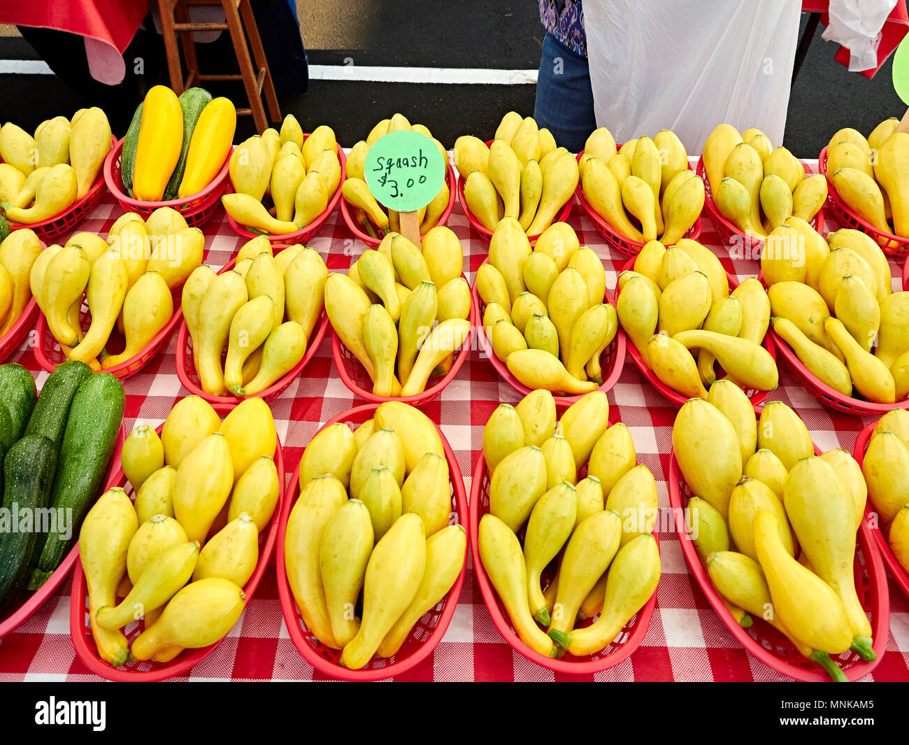 Baskets of fresh yellow squash or summer squash on display, for sale, at a local farmer's market in Montgomery Alabama, USA. - Stock Image