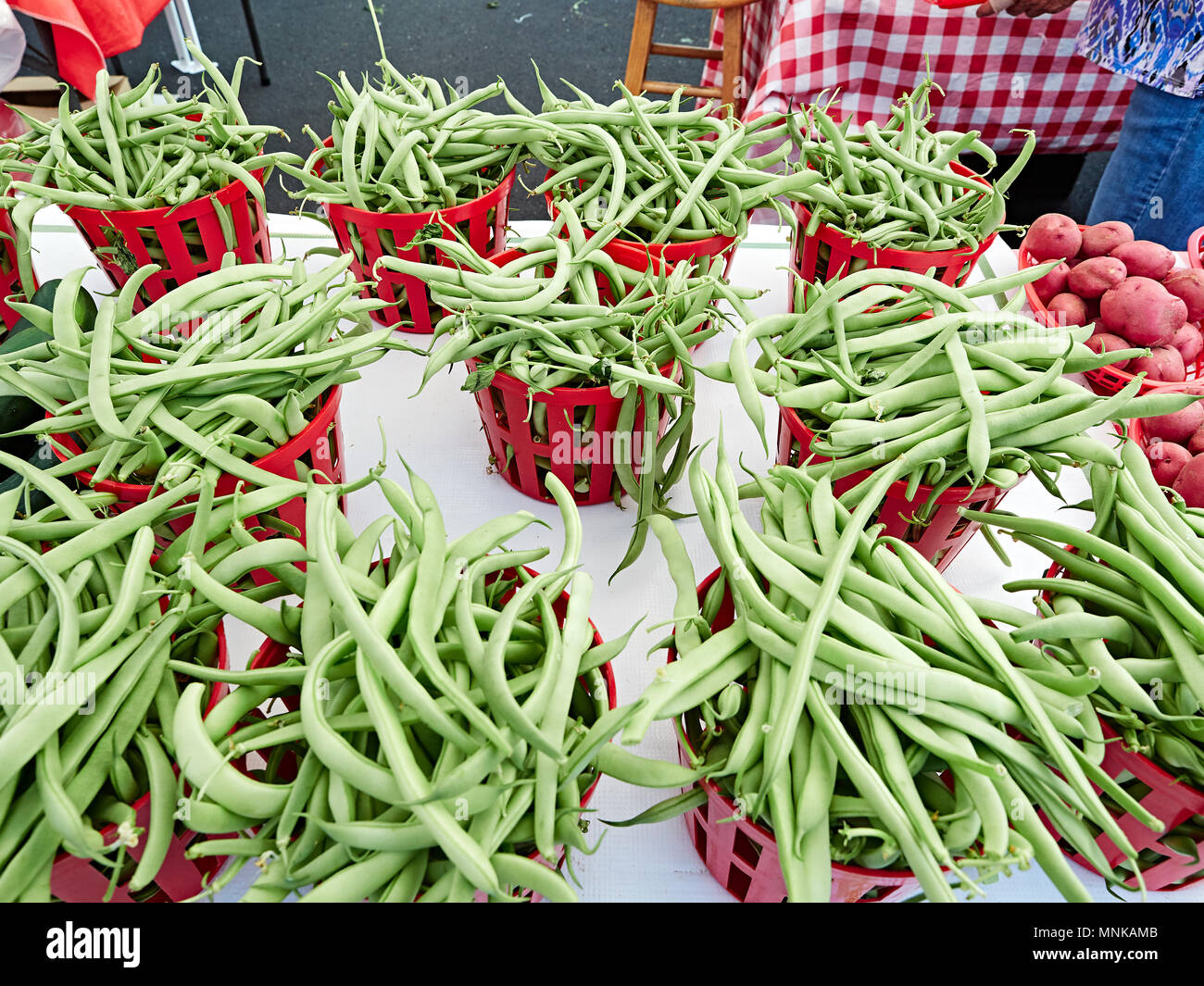 Baskets of green snap beans or green beans, on display, for sale, at a local farmer's market in Montgomery Alabama, USA. - Stock Image