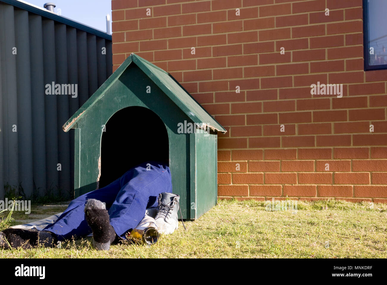 A man in the dog house...... literally. - Stock Image
