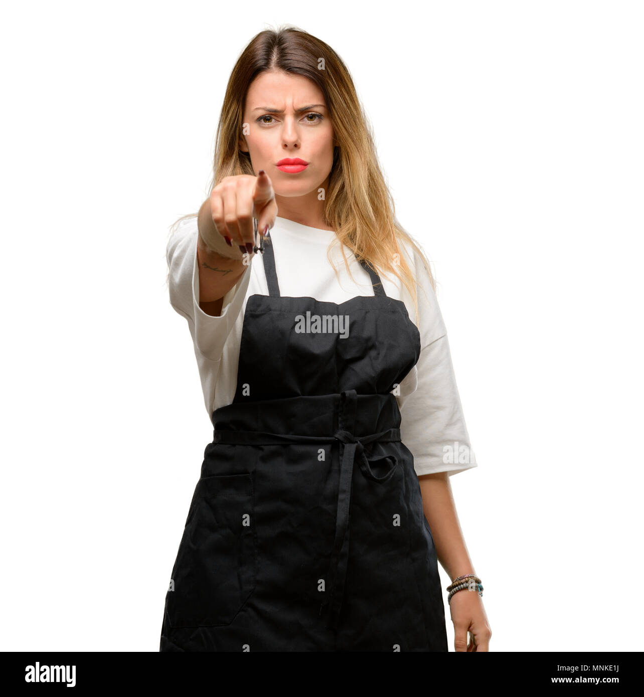 Shop owner woman wearing apron pointing to the front with finger - Stock Image