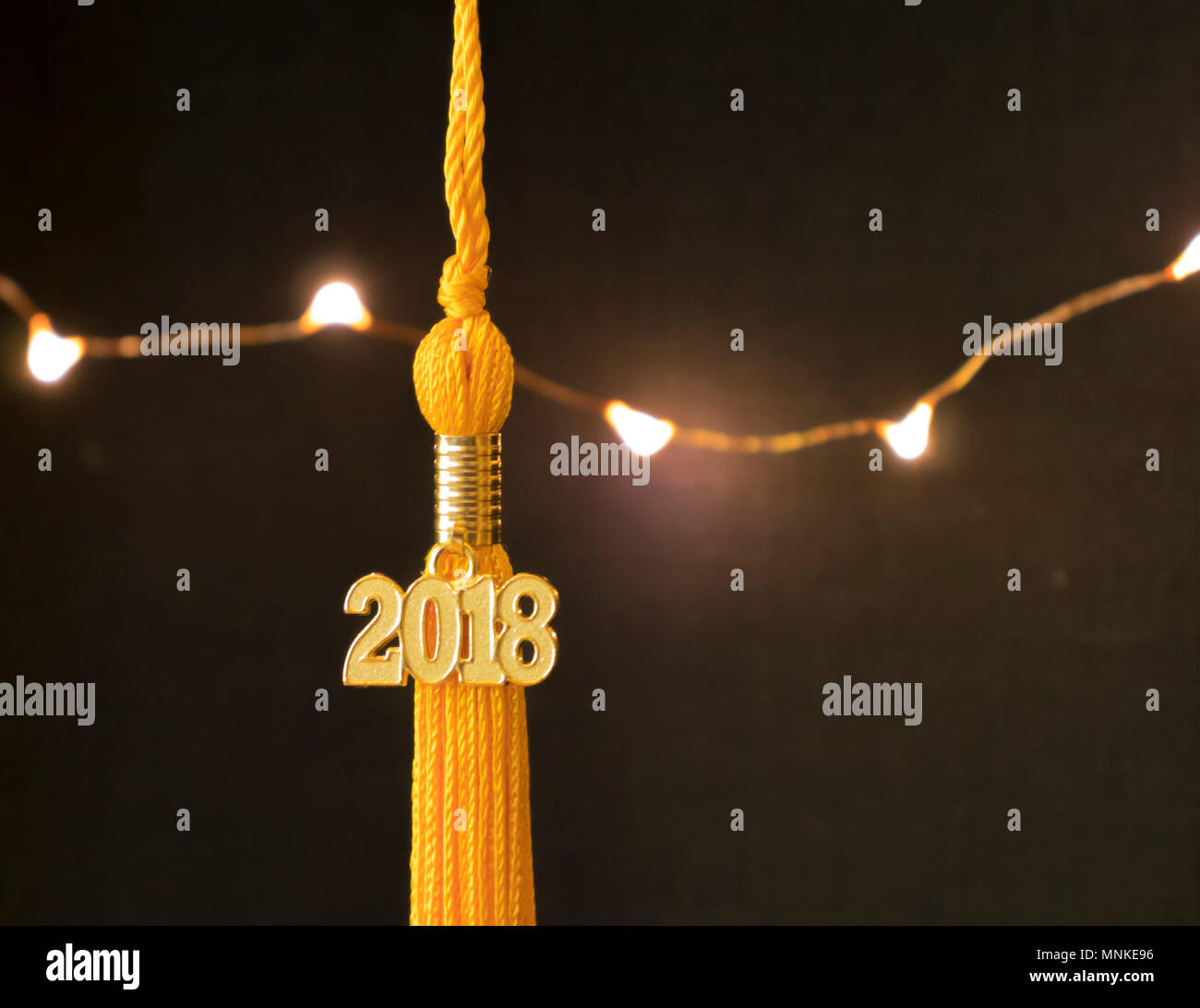 Class of 2018. Gold tassel drop graduation gown accessory and keepsake against a black background and lights. Iconic symbol of academic achievement. - Stock Image