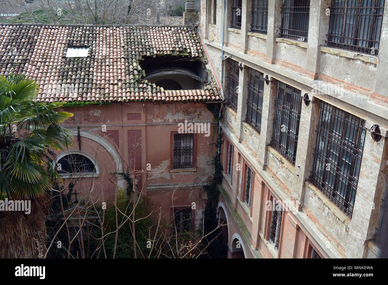 Looking at Hole in Roof of Abandoned Italian Psychiatric Hospital Building from Upper Floor - Stock Image