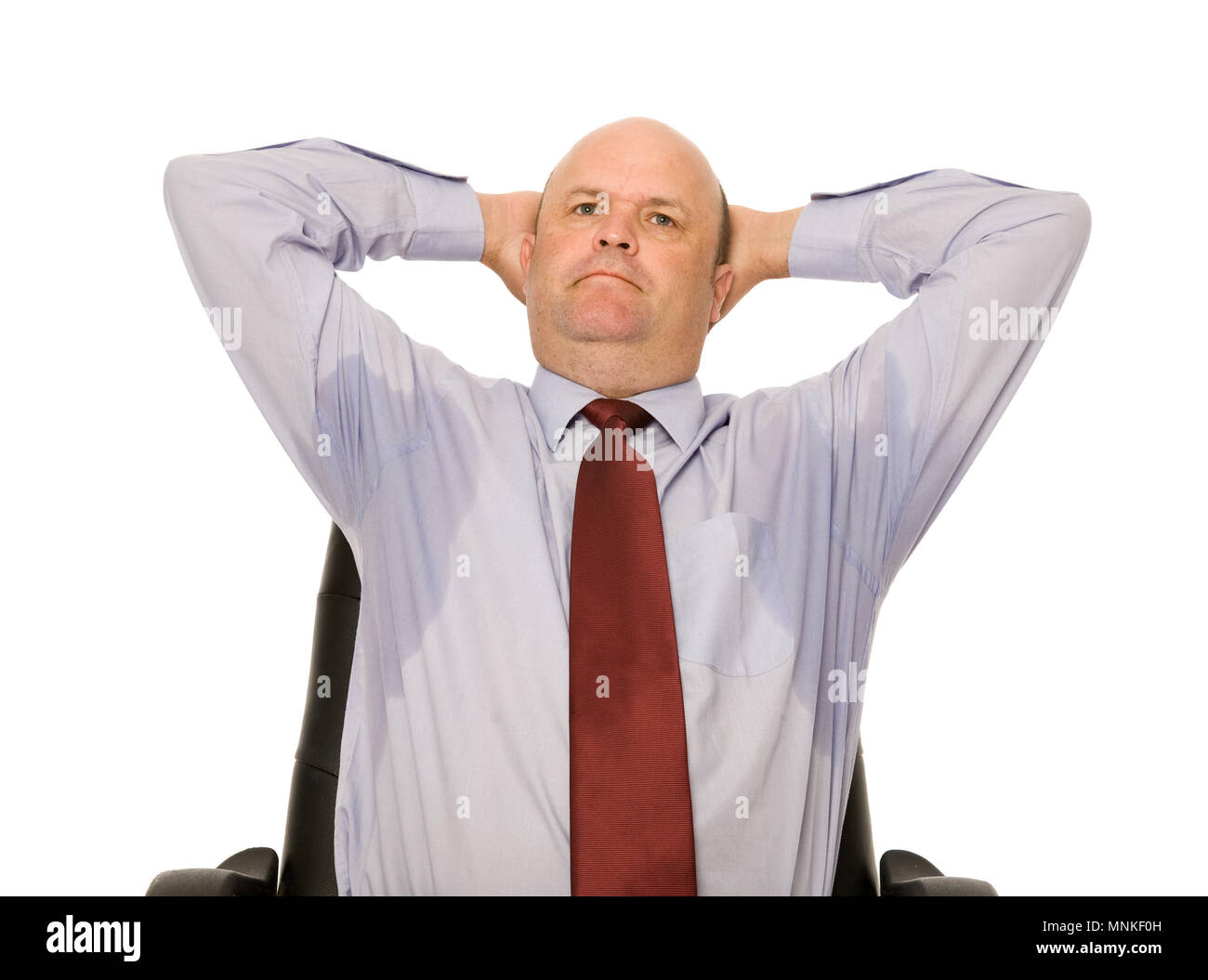 A perspiring businessman, unaware of the sweat stains. - Stock Image