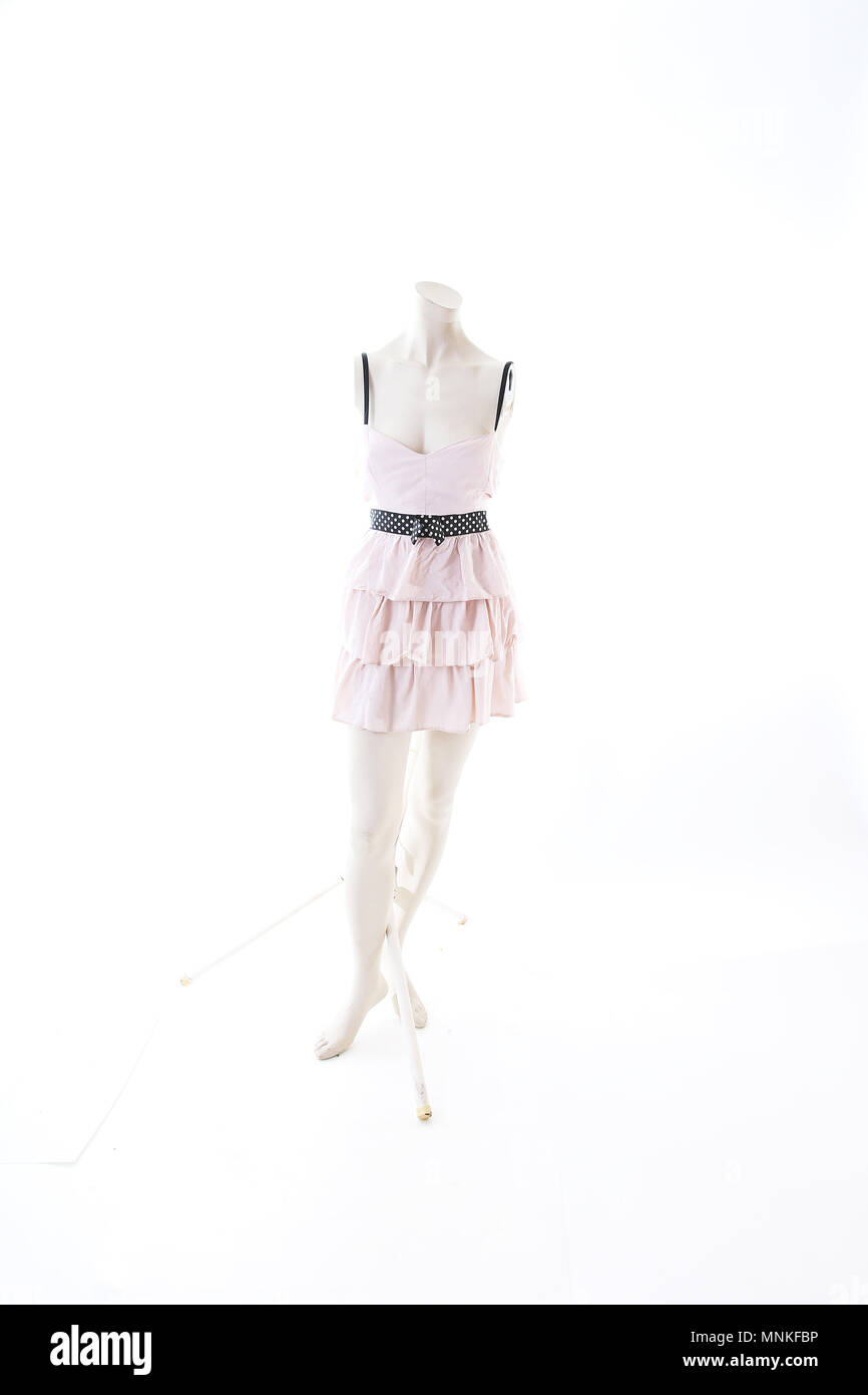 Pink mini dress on mannequin full body shop display. Woman fashion styles, clothes on white studio background. - Stock Image