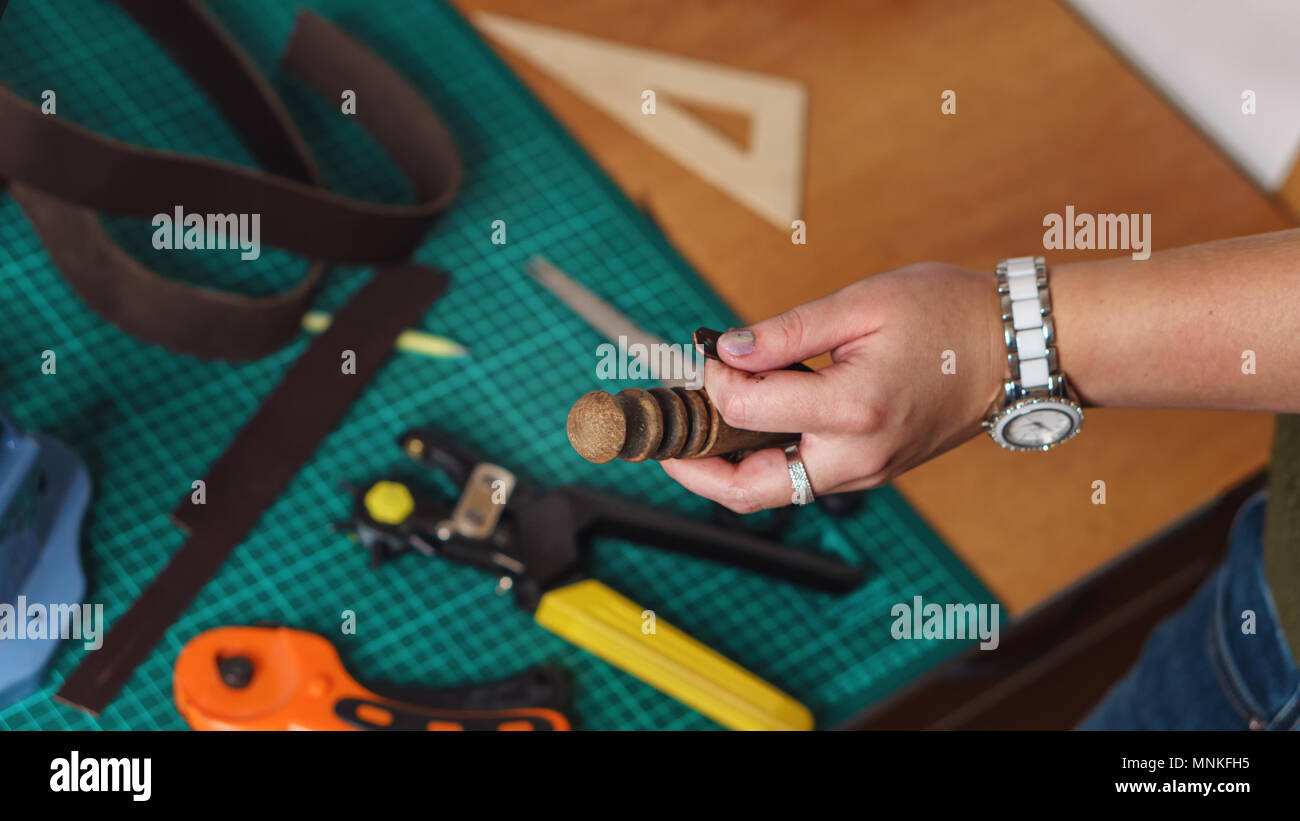 Tanner holds slicker and leather blank in her hands. In background lie knife, punch and rulers. Workflow in workshop. Shooting close-up. - Stock Image
