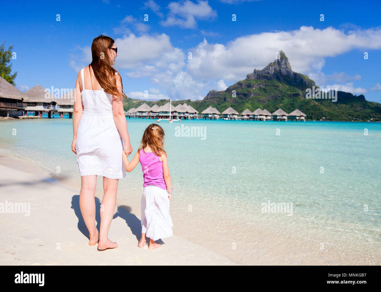 Mother and daughter at tropical beach enjoying view of Otemanu mountain - Stock Image