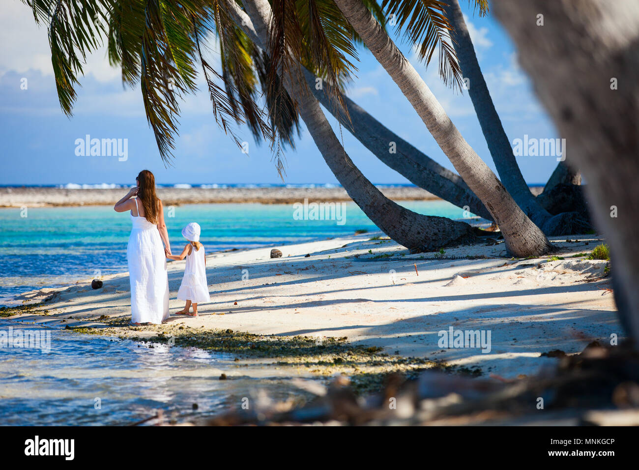Back view of mother and daughter on a deserted island - Stock Image