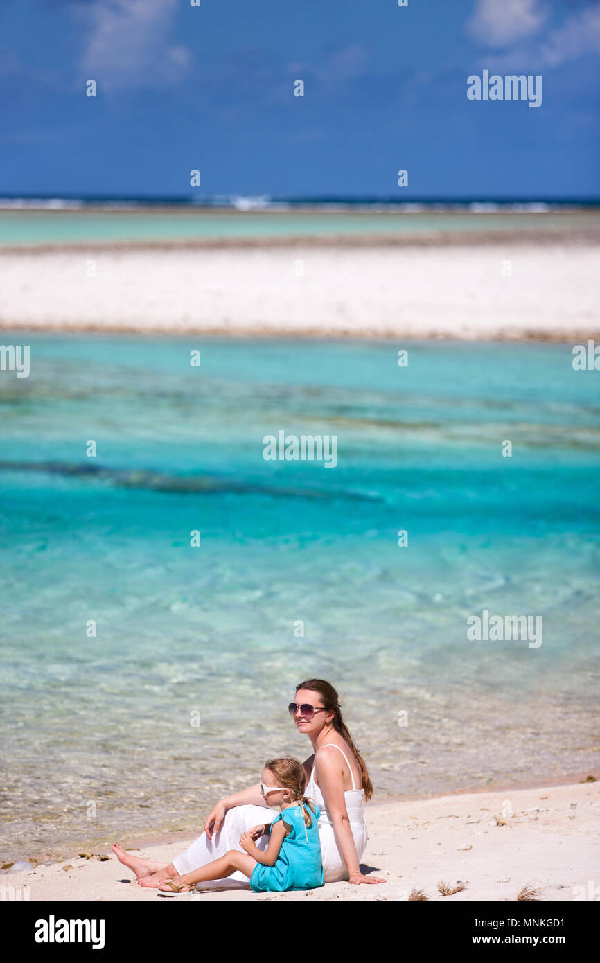 Beautiful mother and daughter sitting on a deserted tropical beach - Stock Image