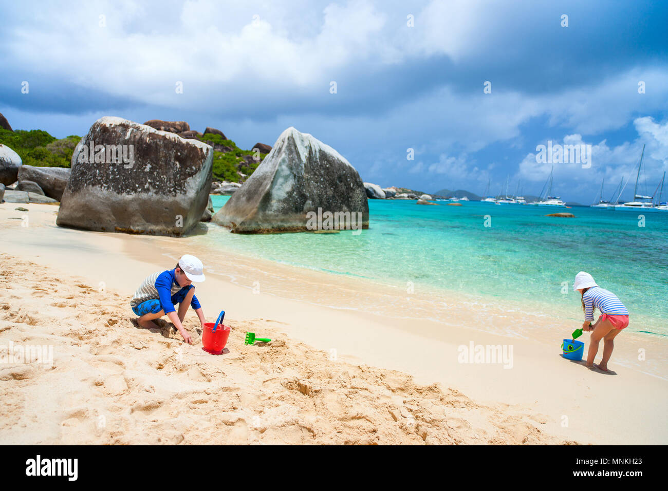 Kids wearing sun protection rash guard playing at beach during summer vacation - Stock Image