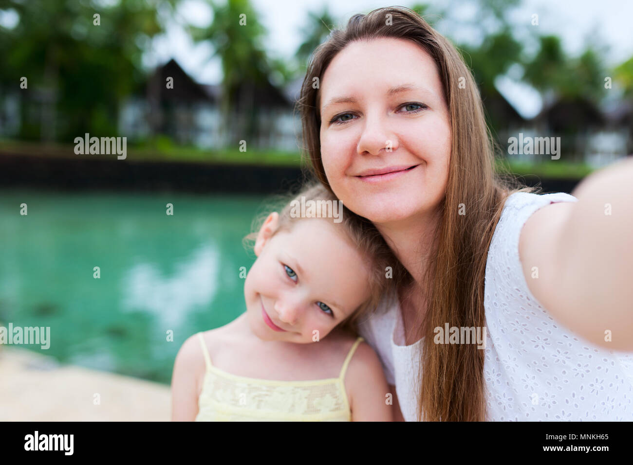 Happy family mother and her adorable little daughter on summer vacation taking selfie with smartphone - Stock Image