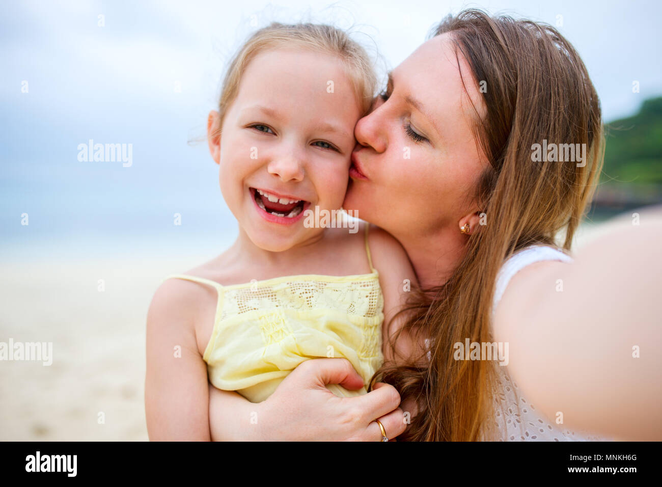 Happy family mother and her adorable little daughter at beach making selfie - Stock Image