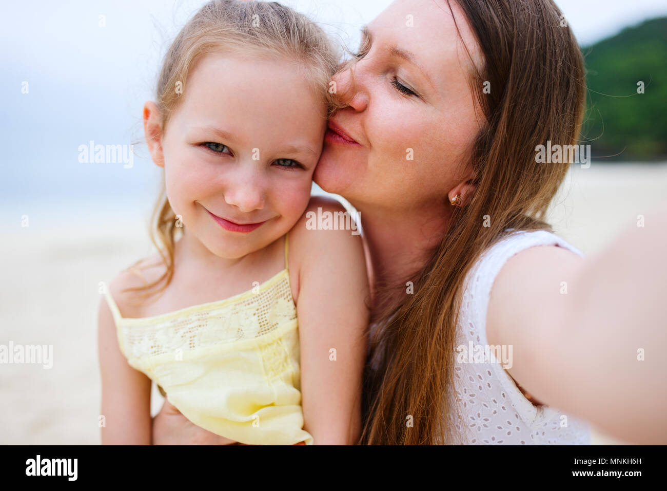 Happy family mother and her adorable little daughter at beach taking selfie - Stock Image