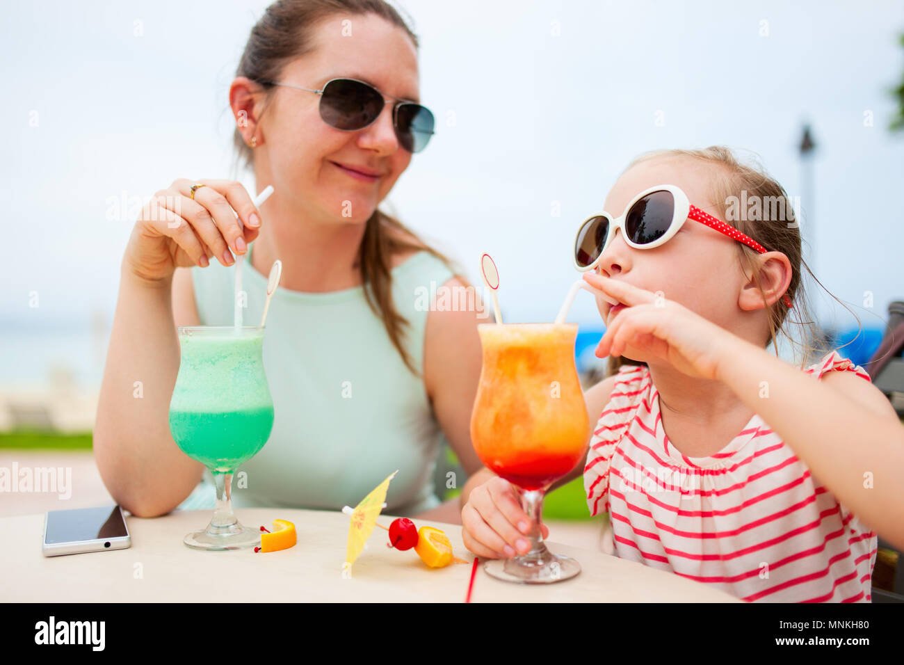 Happy mother and her adorable little daughter at outdoors cafe drinking tropical juice - Stock Image