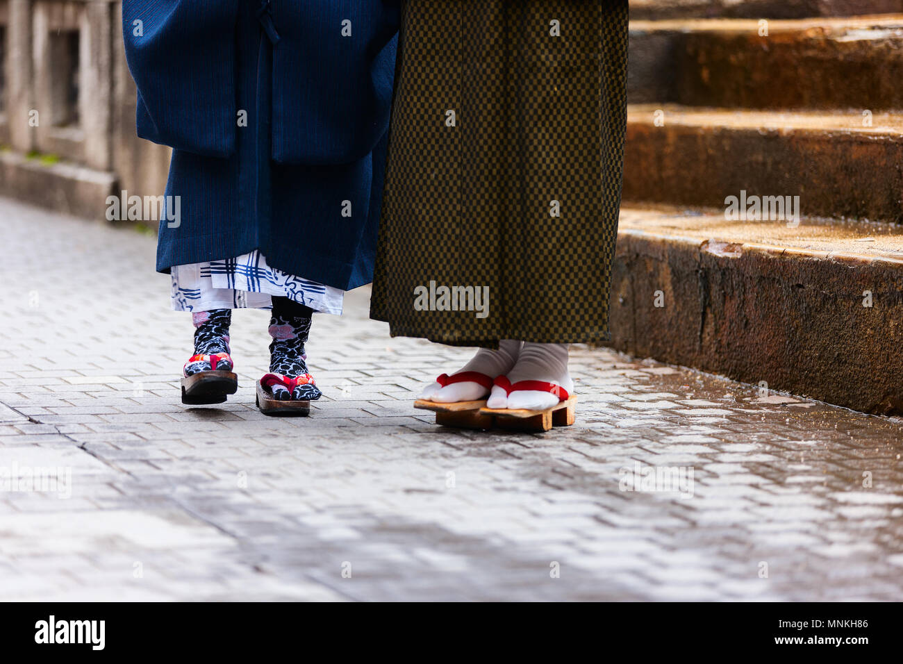 Close up of mother and daughter wearing kimono and geta traditional Japanese footwear. - Stock Image