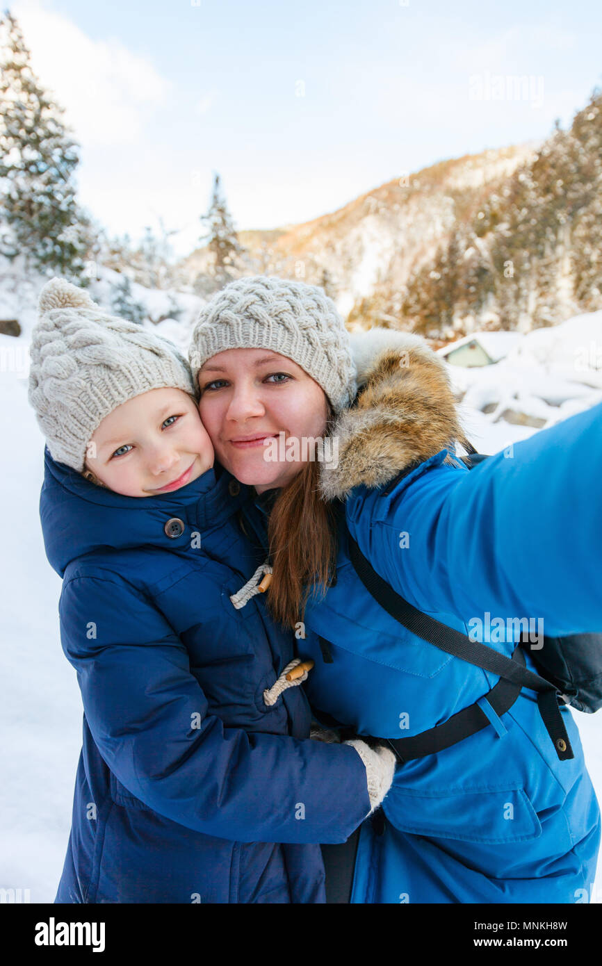 Mother and doughter taking selfie on beautiful winter day outdoors - Stock Image