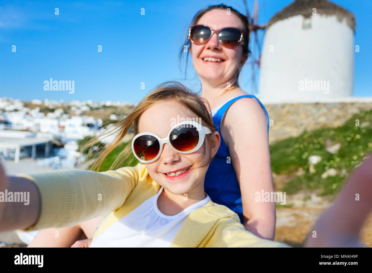 Happy family mother and her adorable little daughter on vacation taking selfie at Little Venice area on Mykonos island, Greece - Stock Image