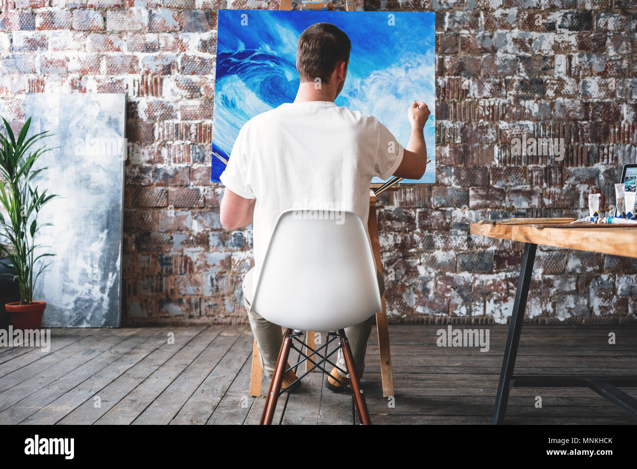 Man artist sitting on chair in front of canvas on easel and drawing. Painter working in workshop. Art handiwork - Stock Image