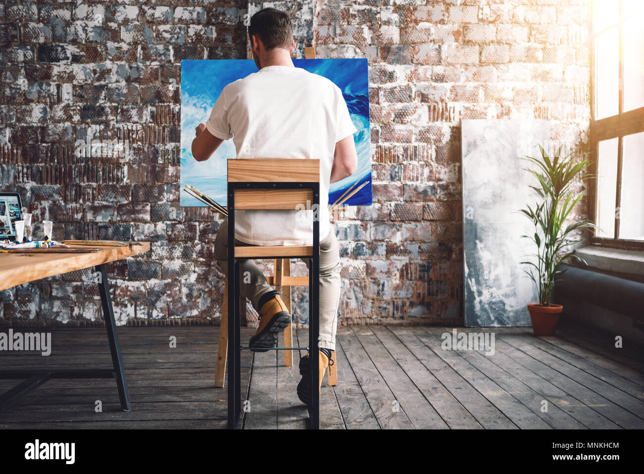 Male painter sits on chair in front canvas and drawing picture in studio. Art class and workshop. Artist painting process. Hobby - Stock Image
