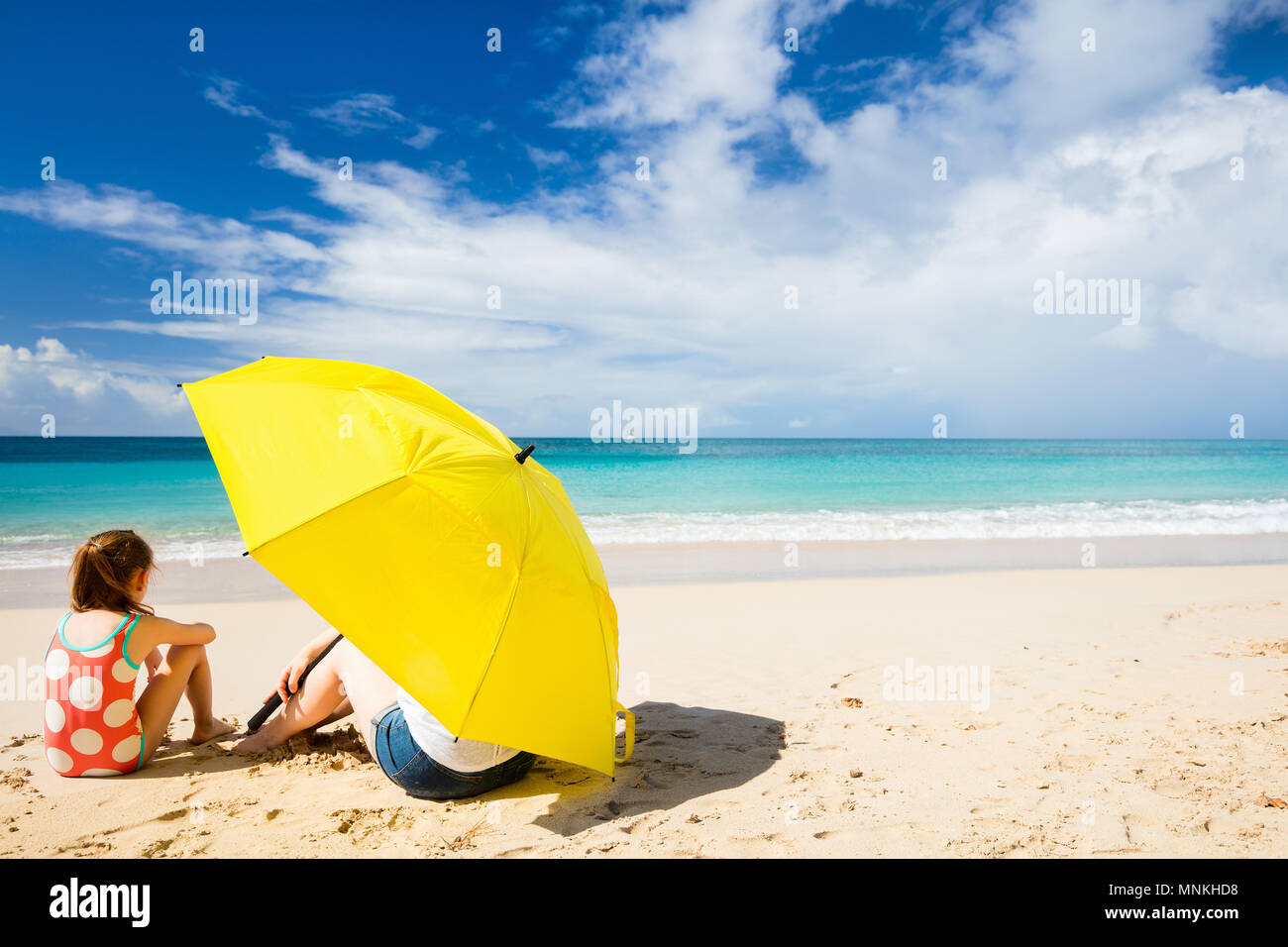 Mother and daughter with big yellow umbrella hiding from sun at tropical beach - Stock Image