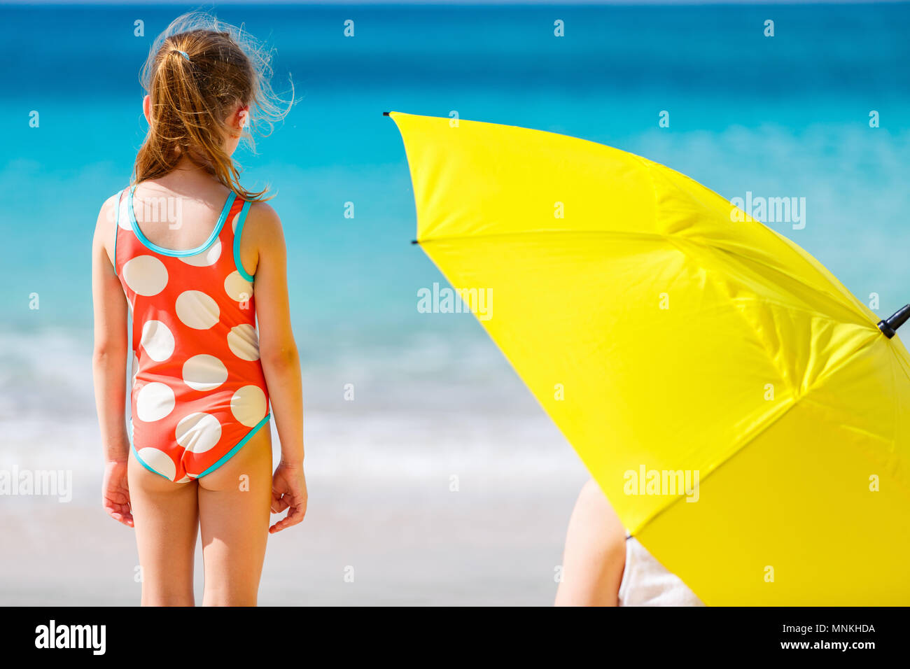 Cute little girl and her mother with big yellow umbrella hiding from sun at tropical beach - Stock Image