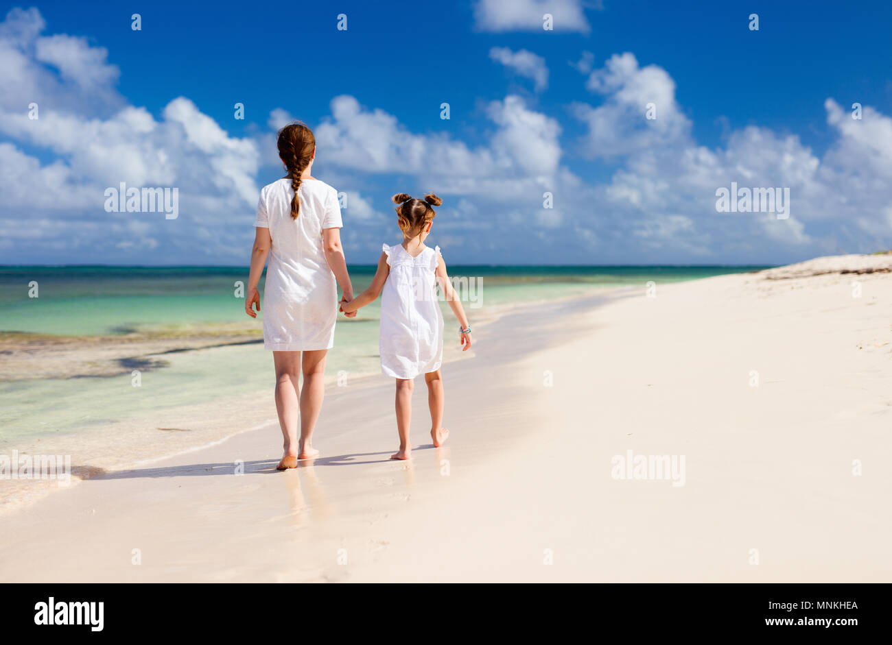 e8292ebf6139f Back view family mother and daughter walking at beach enjoying tropical summer  vacation