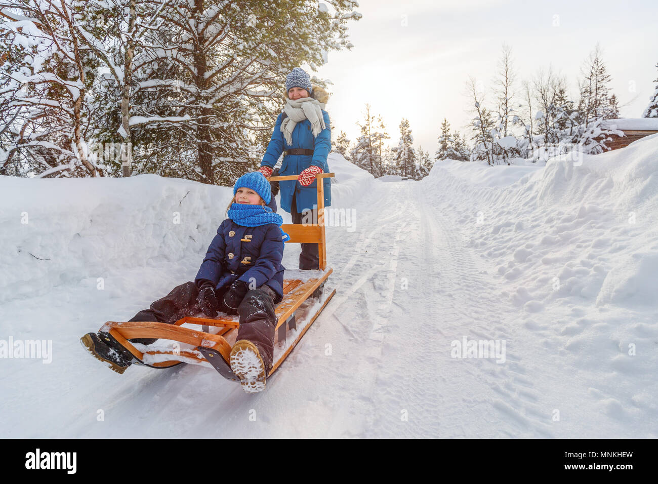Beautiful family of mother and daughter enjoying snowy winter day outdoors having fun sledging - Stock Image