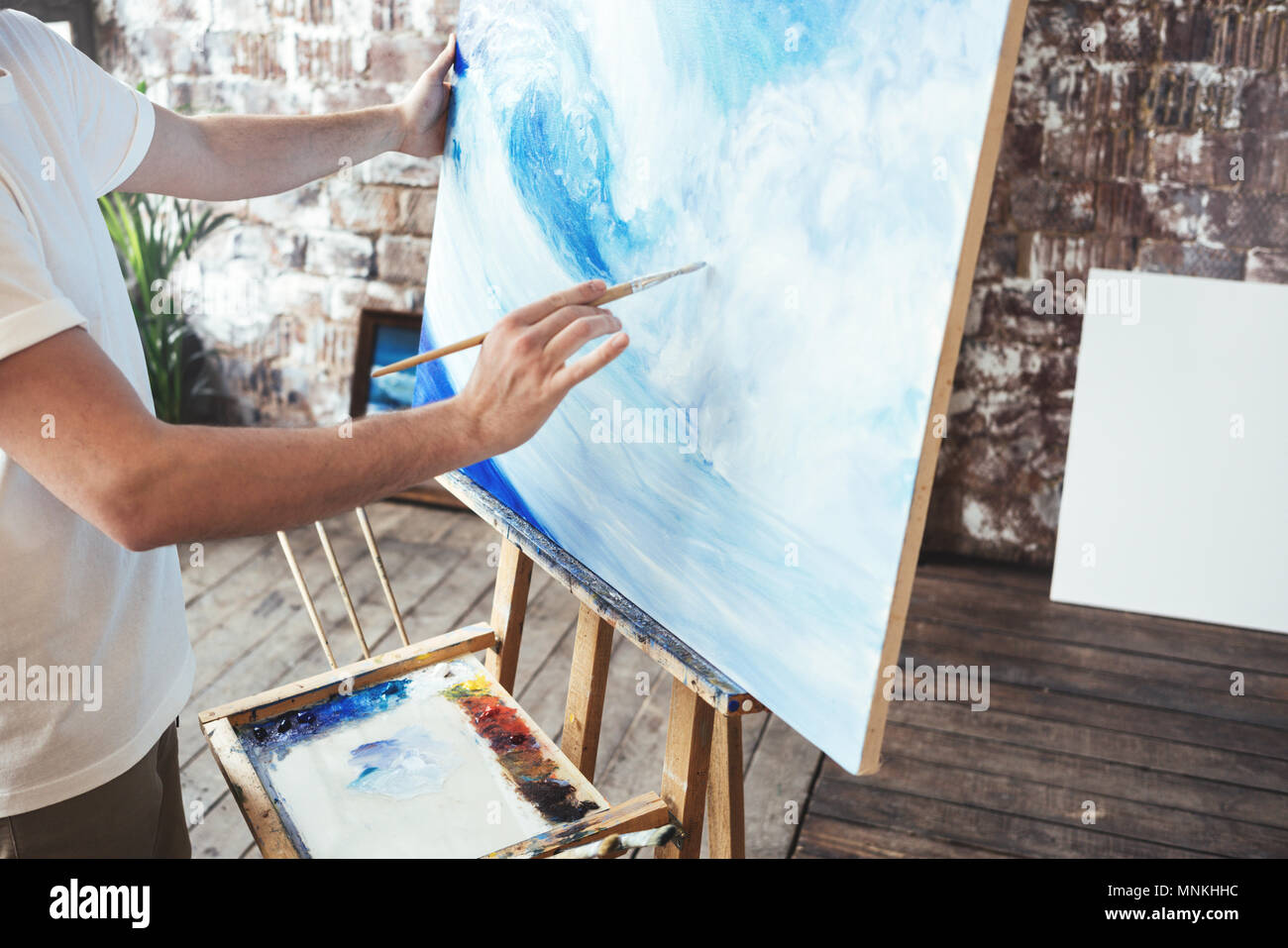 Process of drawing with oilpaints and paintbrush. Artist paints on canvas painting on easel in studio. Hobby - Stock Image