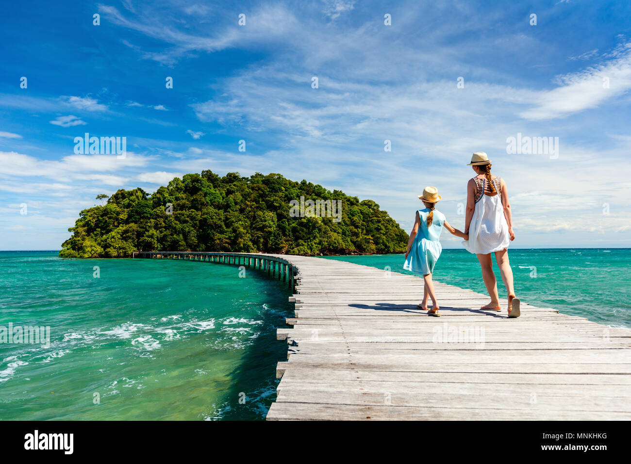 Family walking on wooden pathway leading to beautiful tropical island in Cambodia - Stock Image