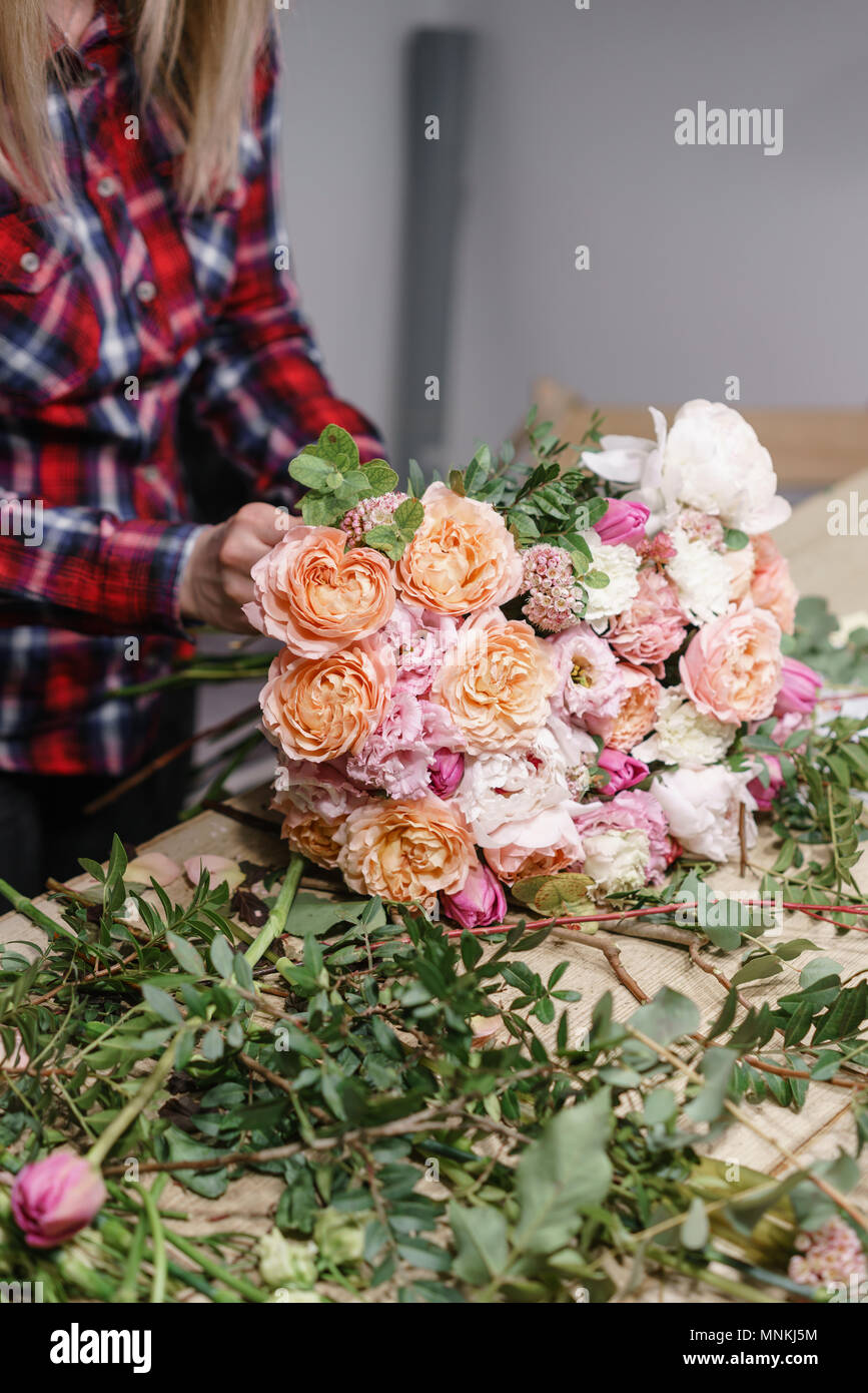Female florist. Floral workshop - woman making a beautiful flower composition a bouquet. Floristry concept Stock Photo