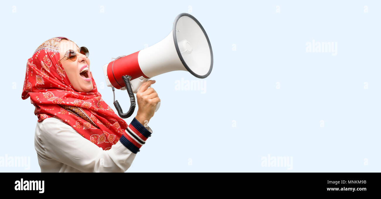 Middle age muslim arab woman wearing hijab communicates shouting loud holding a megaphone, expressing success and positive concept, idea for marketing - Stock Image