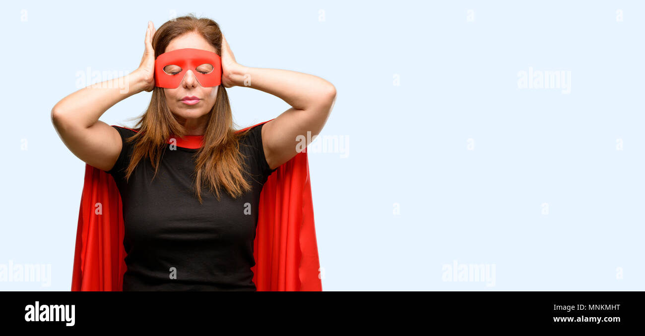 Middle age super hero woman wearing red mask and cape covering ears