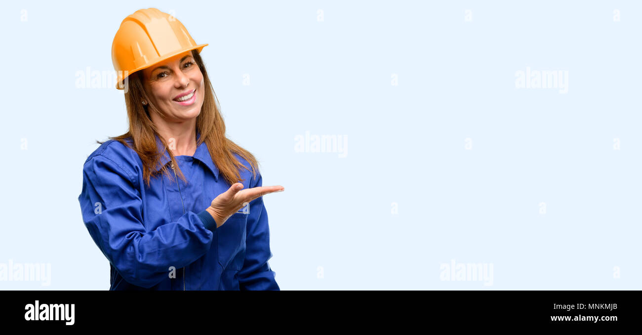 Engineer construction worker woman holding something in empty hand isolated blue background - Stock Image