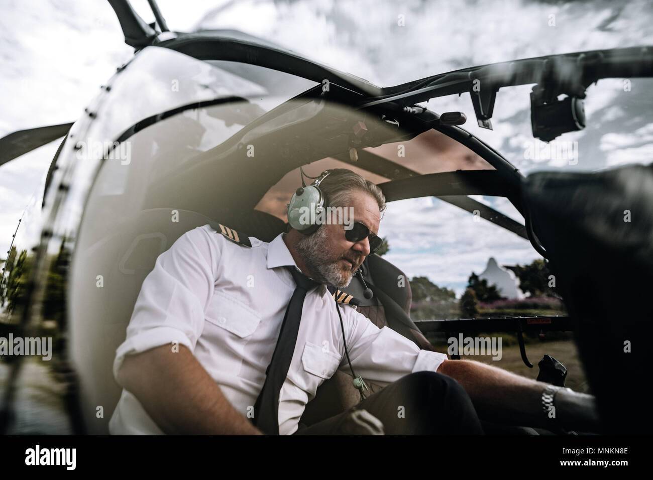 Male pilot operate switches of helicopter system prior to departure. Pilot sitting inside helicopter cockpit. - Stock Image
