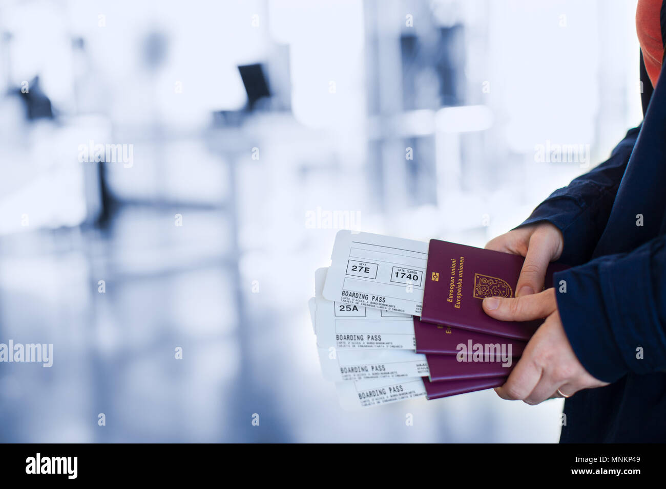 Close up of woman holding passports and boarding passport at airport - Stock Image
