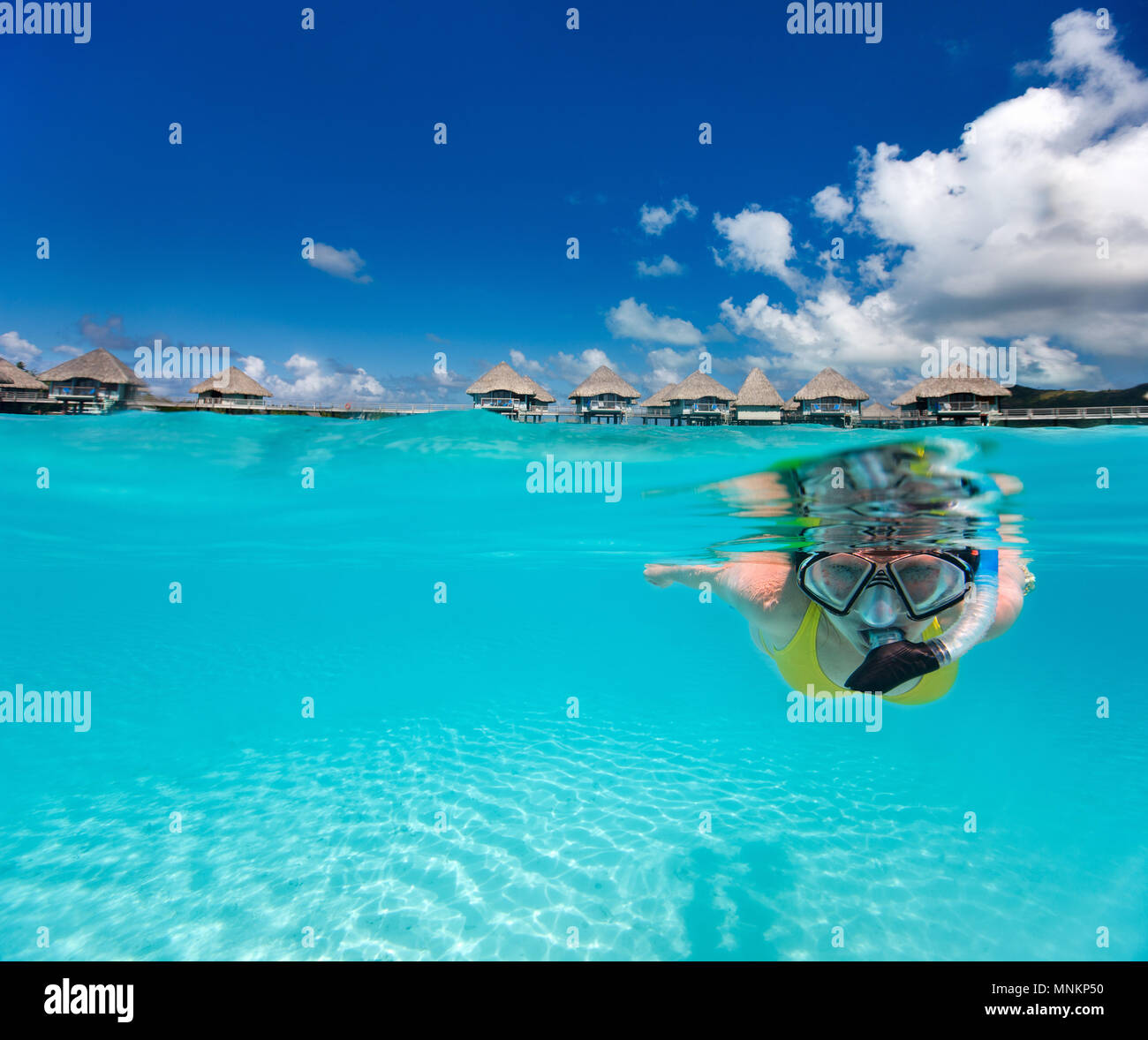 Underwater photo of woman snorkeling in clear tropical waters in front of overwater villas - Stock Image
