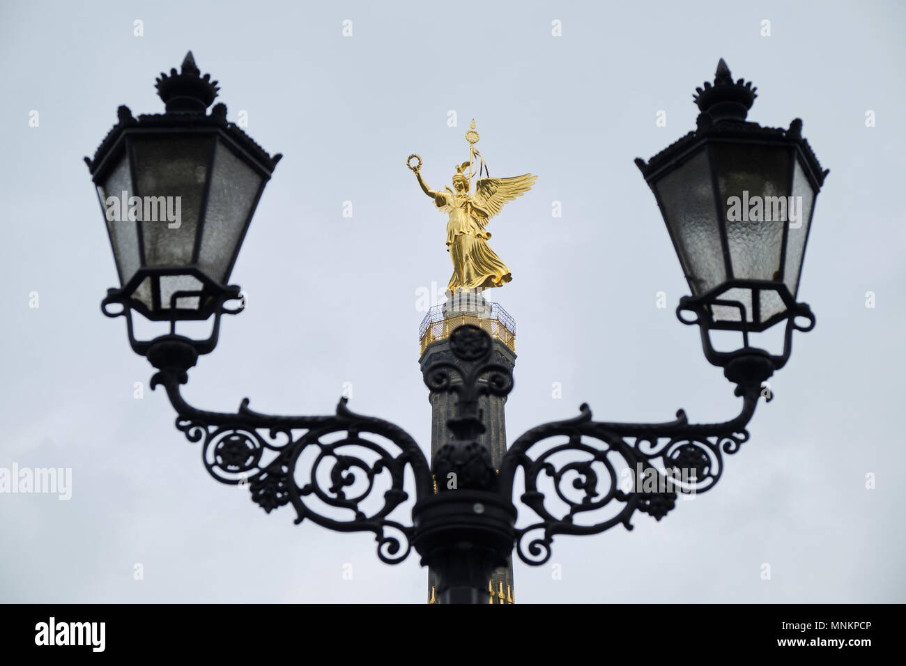 Berlin, Germany - April 14, 2018: The statue of Victoria on the top of the Victory Column in Tiergarten with lantern lamps on the foreground - Stock Image