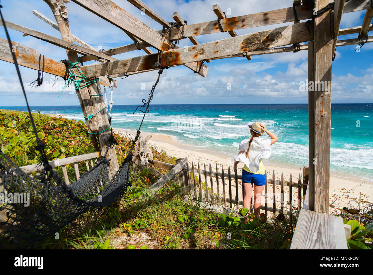 Young woman enjoying view of tropical beach on Eleuthera Bahamas - Stock Image