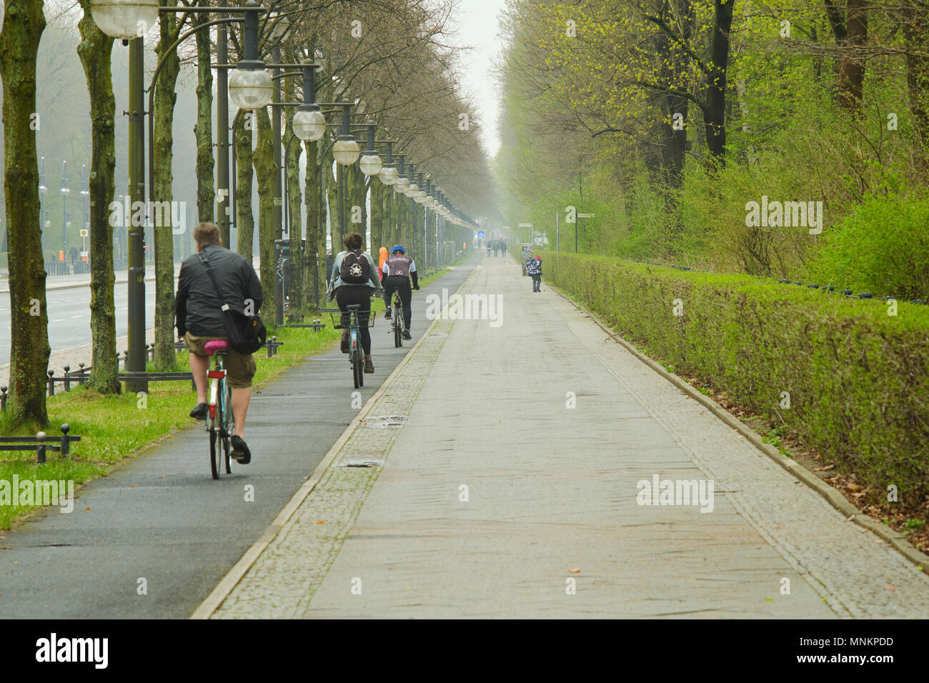 Berlin, Germany - April 14, 2018: Bicycle lane with bicyclists and sidewalk along 17th of June Street and Rose garden im Tiergarten, Berlin Stock Photo