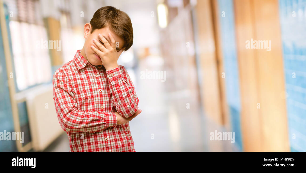 Handsome toddler child with green eyes stressful keeping hands on head, tired and frustrated at school corridor - Stock Image