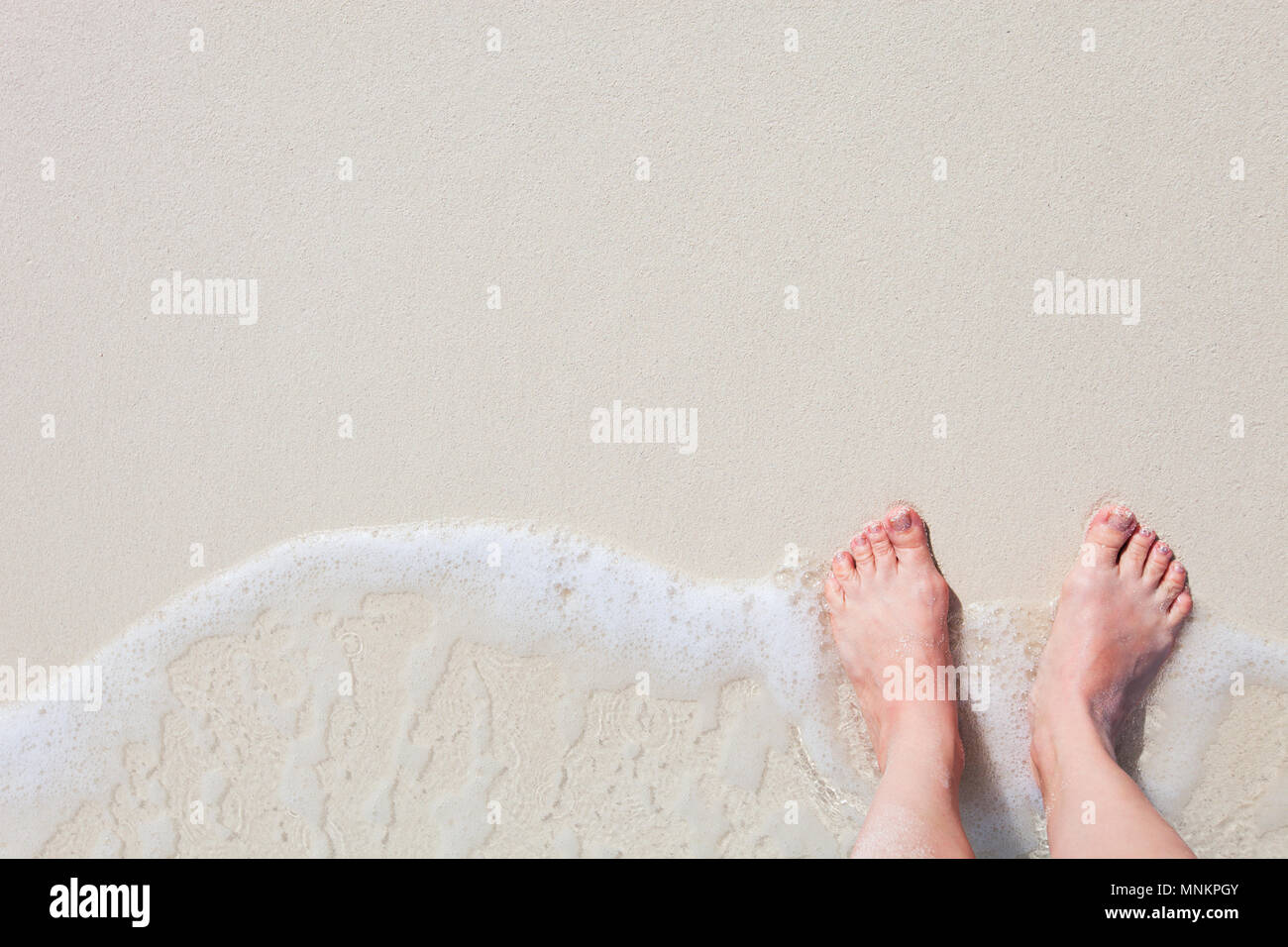 Close up of young woman feet on a tropical sandy beach - Stock Image