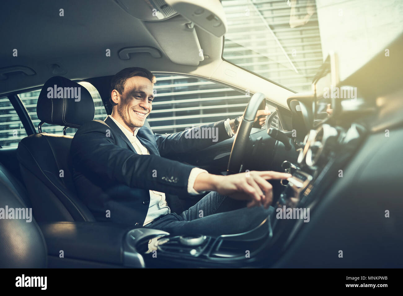 Smiling young businessman wearing a blazer changing radio stations while driving his car through the city during his morning commute to work - Stock Image