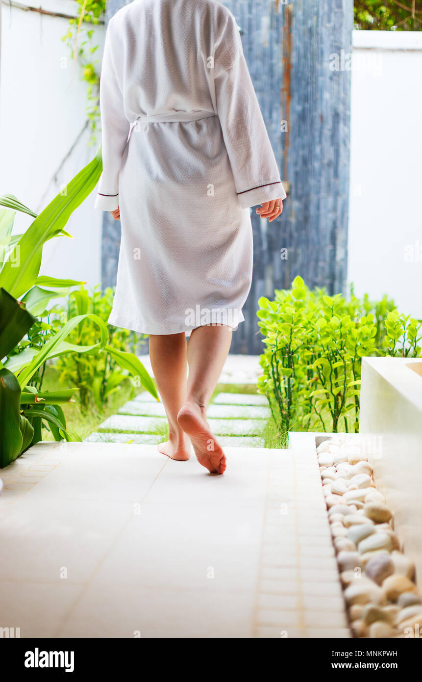 Close up of a woman wearing white robe walking at outdoor spa treatment room - Stock Image