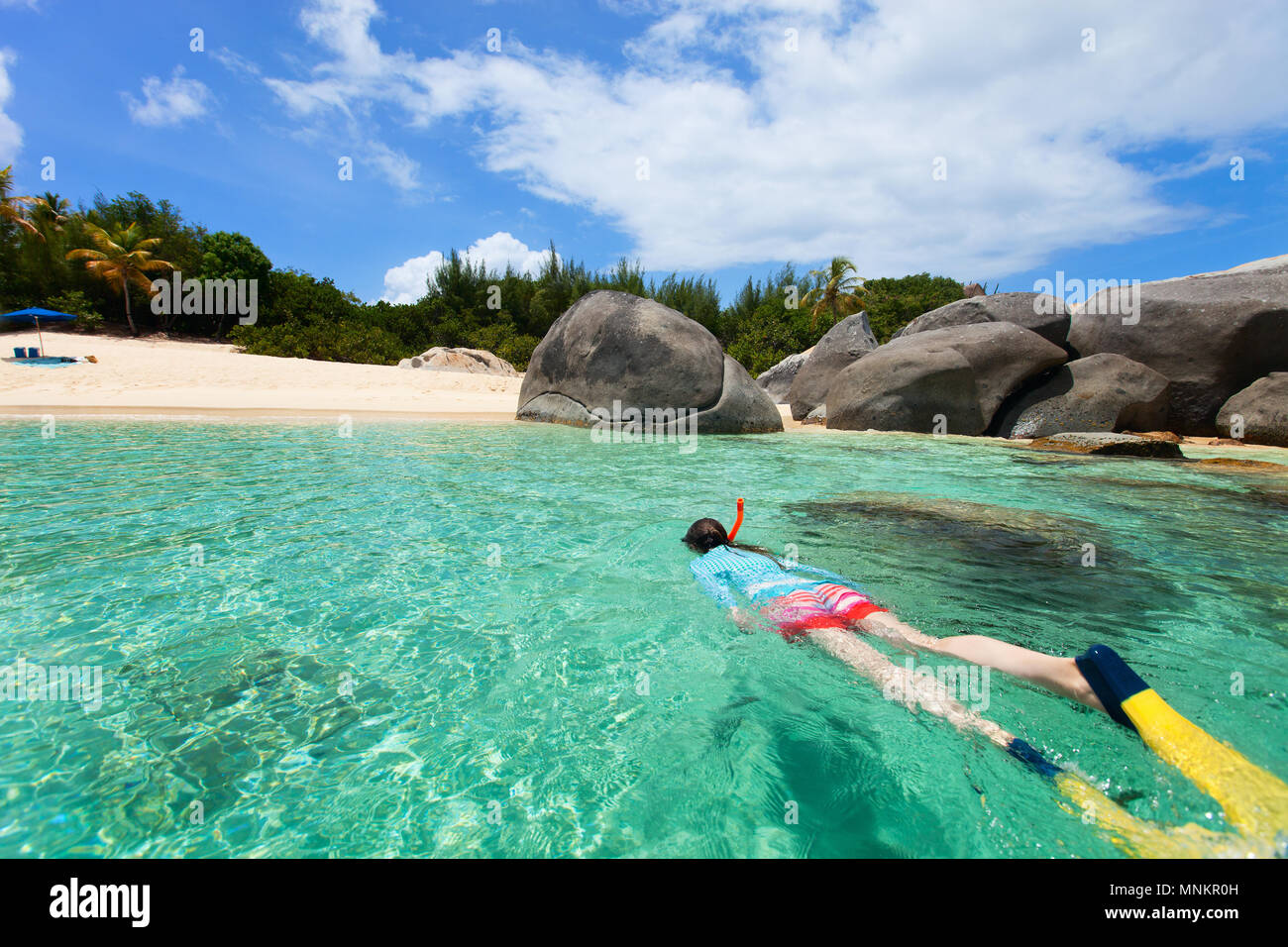 Young woman in sun protection swimwear snorkeling in turquoise tropical water at exotic island beach - Stock Image